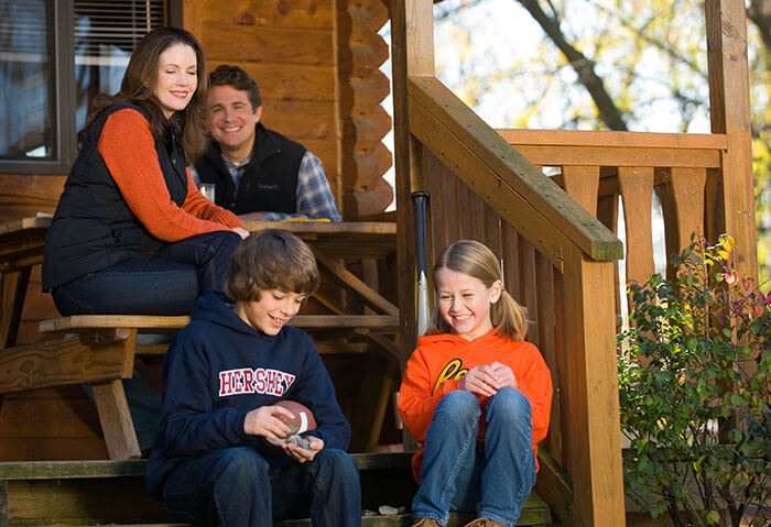 Family on the porch of a cabin dressed for cool weather