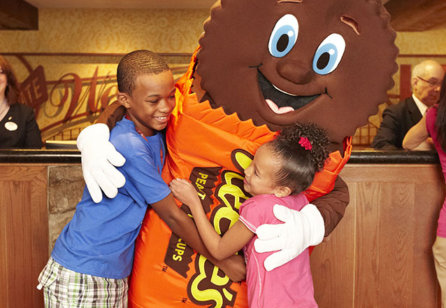Kids hugging Reeses character at Checkin