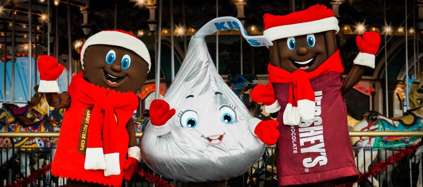 Hershey's Characters, Reese, Kiss, and Hersheybar standing in front of the carrousel waving while wearing Christmas hats, scarves and gloves