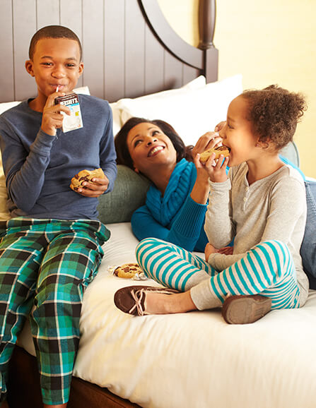 Mom and two children laying in bed eating milk and cookies while wearing warm jammies