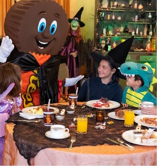 Kids in costume eating a meal with Reese character